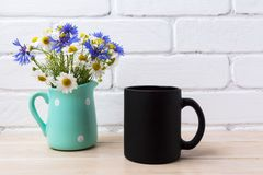 Black coffee mug mockup with cornflower and daisy in pitcher Royalty Free Stock Photography