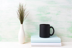 Black coffee mug mockup with dark meadow grass in vase and books Royalty Free Stock Photography