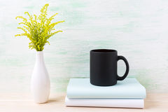 Black coffee mug mockup with ornamental green grass and books Stock Photo