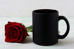 Black coffee mug mockup with red rose Royalty Free Stock Images