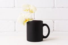 Black coffee mug mockup with soft yellow orchid Royalty Free Stock Images
