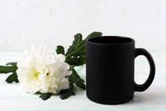 Black coffee mug mockup with white chrysanthemum Royalty Free Stock Photo