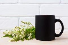 Black coffee mug mockup with white spiraea flowers stock images