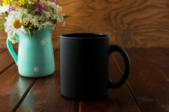 Black coffee mug rustic mockup with wildflowers in mint green va. Black coffee mug rustic mockup with purple, yellow and white wildflowers in the mint green Royalty Free Stock Photos