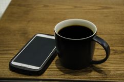 Black coffee mug on wooden table. Black coffee and mug on wooden table Stock Images