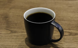 Black coffee mug on wooden table. Black coffee and mug on wooden table Royalty Free Stock Photo
