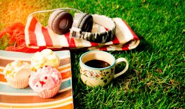 Black coffee mugs lay on the grass with sweets Candy, with a mus. Coffee and music in the garden and relaxation Stock Images