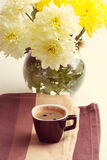Black coffee near the yellow flowers Stock Image
