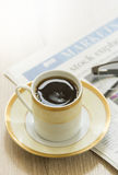 Black coffee and newspaper. Royalty Free Stock Images