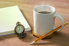 Black coffee with a notebook on a brown table. In the morning and Vintage clock at 8 o'clock stock photo