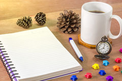 Black coffee with a notebook on a brown table. In the morning and Vintage clock at 8 o'clock. Paper stars and pine cones laid on wooden table stock images