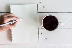 Black coffee with notebook and pencil on wooden background. Black coffee with notebook and pencil on a wooden background Royalty Free Stock Image