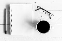 Black coffee with notebook and pencil on wooden background - bla. Black coffee with notebook and pencil on a wooden background - black and white Royalty Free Stock Photography