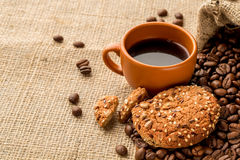 Black coffee with a oatmeal. Cookies on burlap background Stock Photography