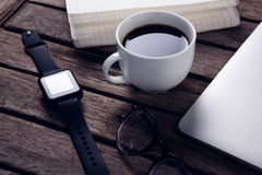 Black coffee with organizer, laptop, spectacles and smart watch on wooden table. Close-up of black coffee with organizer, laptop, spectacles and smart watch on Stock Photos