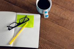 Black coffee with organizer, spectacles, pen and sticky note on wooden table. Close-up of black coffee with organizer, spectacles, pen and sticky note on wooden Royalty Free Stock Photography