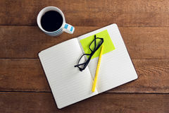 Black coffee with organizer, spectacles, pen and sticky note on wooden table. Overhead view of black coffee with organizer, spectacles, pen and sticky note on Stock Image
