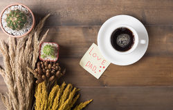 Black coffee with paper note wood background. Black coffee with paper note and cactus on old wood background, concept love dad Royalty Free Stock Photography