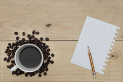 Black coffee, pencil and notepaper on wood table Stock Photos