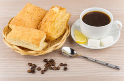 Black coffee, pieces of lemon and sugar, flaky biscuits Stock Image