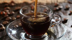 Black coffee is poured into glass transparent cup on saucer stock video footage