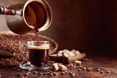 Black coffee is poured into a small glass cup from a copper coffee maker. Coffee beans and brown sugar pieces on a old table. Copy space stock images