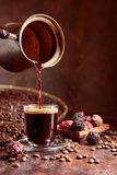 Black coffee is poured into a small glass cup from a copper coffee maker. Coffee beans and chocolate truffles on a old table. Copy space royalty free stock photography