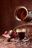 Black coffee is poured into a small glass cup from a copper coffee maker. Coffee beans and chocolate truffles on a old table. Copy space stock images