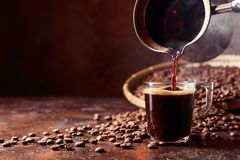 Black coffee is poured into a small glass cup from a old copper coffee maker. Copy space.  stock photography