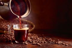 Black coffee is poured into a small glass cup from a old copper coffee maker. Copy space royalty free stock photos