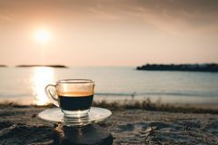 Black coffee ready to drink from mug on the beach outdoor picnic. Hot esspresso shot or hot black coffee from mokka pot ready to serve at freshy morning time on royalty free stock image