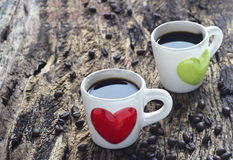 Black coffee in red and green heart cup on wooden Stock Images