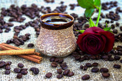Black coffee with a rose. Coffee with cinnamon and rose on a background of coffee beans. Sackcloth Royalty Free Stock Photography