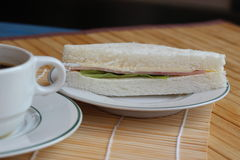 Black coffee and sandwich lay on a brown background.  Royalty Free Stock Photos