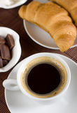 Black coffee served with croissant Royalty Free Stock Images