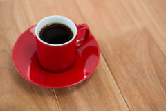 Black coffee served in red cup Royalty Free Stock Image