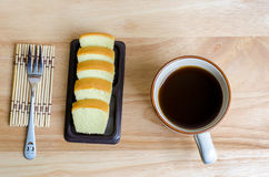 Black Coffee and slice of butter cake on wooden table Stock Photo