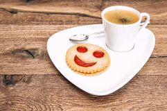 Black coffee smiled cookie Funny breakfast. Black coffee and smiled cookie on wooden background. Funny breakfast Royalty Free Stock Photo