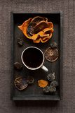 Black coffee and some dried orange slices on wooden tray. Flat l. Some dried orange peel, cones and dried orange slices with a cup of hot dlack coffee on black Stock Image