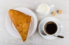 Black coffee, spoon, puff bun, jug of milk and sugar. Black coffee in cup, spoon on saucer, puff bun in plate, jug of milk and sugar on wooden table. Top view stock image
