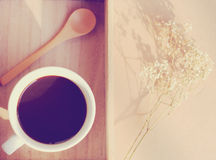 Black coffee and spoon on wooden tray with dried flower Royalty Free Stock Photo
