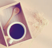 Black coffee and spoon on wooden tray with dried flower Stock Photos