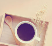 Black coffee and spoon on wooden tray with dried flower Royalty Free Stock Images