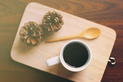 Black coffee and spoon on wooden tray with pine cone, retro filt Royalty Free Stock Photos