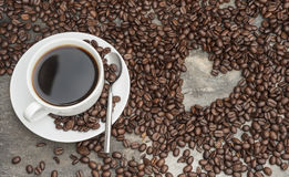 Black coffee surrounded by beans with heart shaped hole, coffee Royalty Free Stock Images
