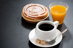Black coffee, sweet bun and orange juice on a black background Stock Images