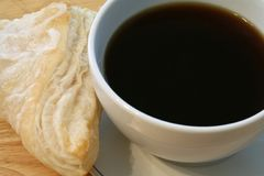 Black coffee and a turnover Royalty Free Stock Image