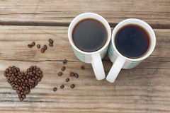 Black Coffee For Two With Heart Shaped Coffee Beans Royalty Free Stock Photography