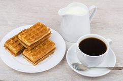 Black coffee with viennese waffles and jug milk on table. Black coffee with viennese waffles and jug milk on wooden table Royalty Free Stock Images