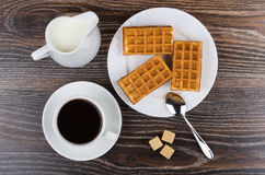 Black coffee with viennese waffles and jug milk on table. Black coffee with viennese waffles and jug milk on wooden table. Top view Royalty Free Stock Image